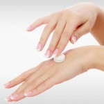 Female hands with a moisturiser on light grey background