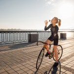 Woman quenches thirst while riding a bike